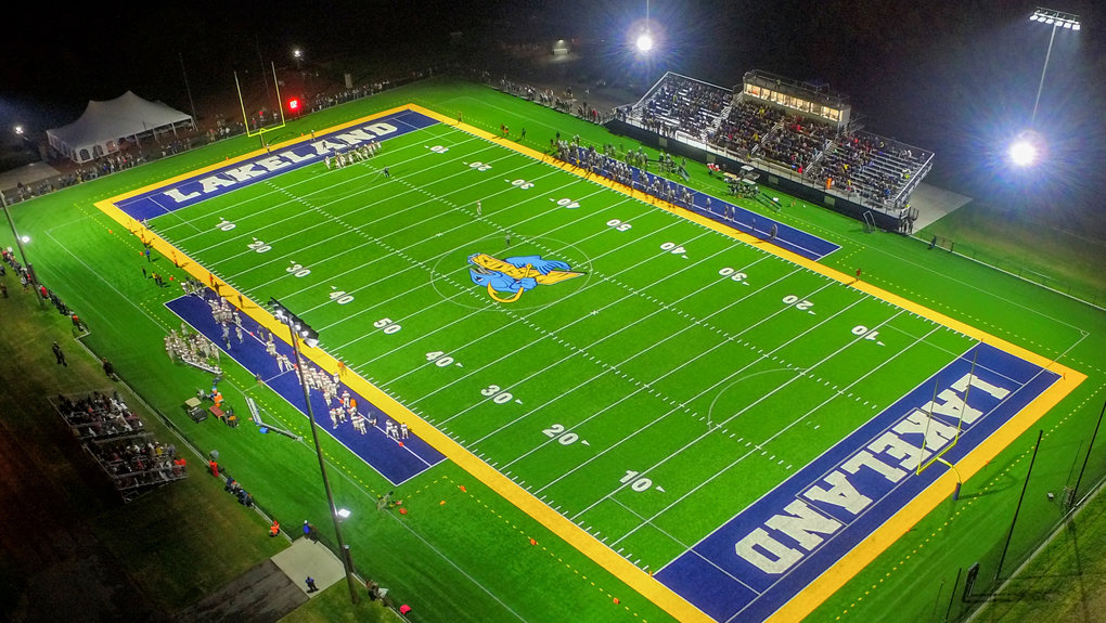 Aerial view of a football game at night on the new turf field.