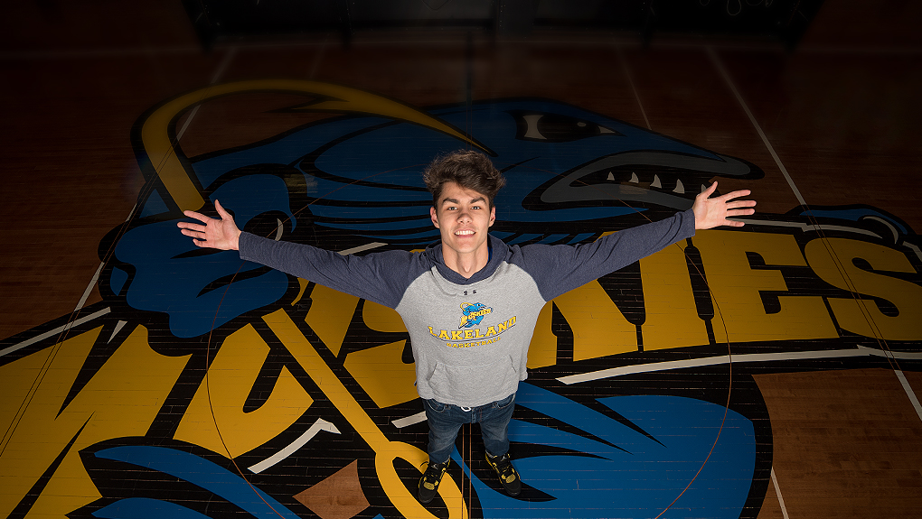 Student standing on the basketball court in front of the Muskies logo.