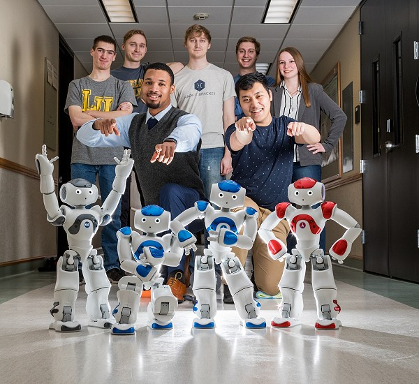Computer Science students posing for picture with Lakeland robots.